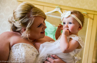 Bride and flower girl share a moment on the morning of the wedding day, by Lilliput Photography, West Midlands Wedding Photographer
