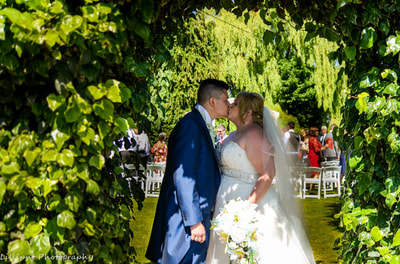 Bride and groom share a kiss after the wedding ceremony, by Lilliput Photography, West Midlands Wedding Photographer