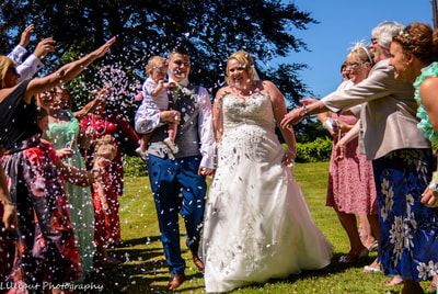 Confetti is thrown at bride and groom by guests at their wedding, by Lilliput Photography, West Midlands Wedding Photographer