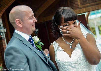 Bride wipes away tears during wedding ceremony in Warwickshire, by Lilliput Photography, West Midlands Wedding Photographer