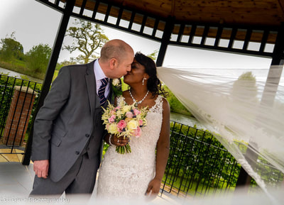 bride and groom share a kiss during wedding portraits by  by Lilliput Photography, West Midlands Wedding Photographer