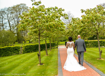 Bride and groom walk through the grounds of their west midlands wedding venue, photographed by by Lilliput Photography, West Midlands Wedding Photographer